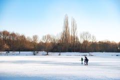 Folk på en djupfryst sjö Arkivfoto