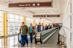 Folk på en rullbandstrottoar i en ljus flygplats Arkivfoto