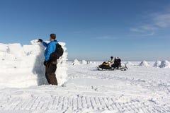 Folk på en snövesslabortgång till och med en djupfryst flod förbi en man som bygger en snövägg Arkivbilder