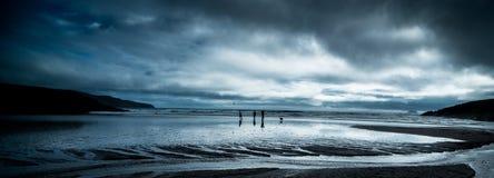Folk på en strand under annalkande stormmoln Royaltyfri Bild
