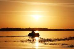 Folk på ett fartyg som håller ögonen på solnedgången på sjön Arkivbild