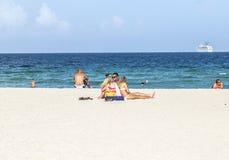 Folk på havssidan i södra strand Arkivbild