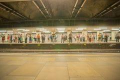 Folk på plattformen för station för milslutrör som går att arbeta och väntar på deras drev för att ankomma arkivfoto
