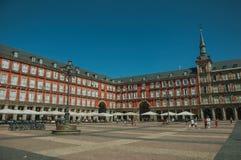 Folk på Plazaborgmästaren med gammal stor byggnad i Madrid royaltyfri fotografi