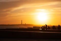 Folk på seacoasten i Marocko på solnedgången royaltyfri bild