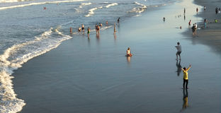 Folk på strand på solnedgången Royaltyfri Fotografi