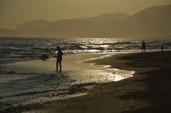 Folk på stranden en solnedgång. Arkivfoton
