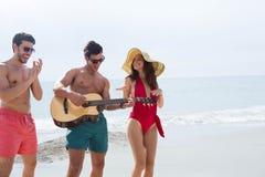 Folk på stranden som spelar gitarren och att dansa Royaltyfria Bilder