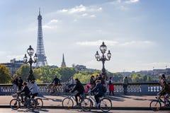 Folk på cyklar och gångare som fritt tycker om en dag för bil på den Alexandre III bron i Paris Arkivfoton