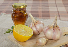 Folk remedies. Garlic, lemon and honey with nuts on a wooden board Stock Photos