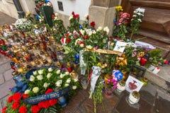 Folk satta stearinljus och blommor nära den allmänna konsulatet av Republiken Frankrike till Krakow Royaltyfria Foton