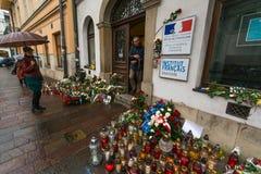 Folk satta stearinljus och blommor nära den allmänna konsulatet av Republiken Frankrike till Krakow Arkivfoto