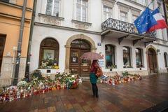 Folk satta stearinljus och blommor nära den allmänna konsulatet av Republiken Frankrike till Krakow Arkivbild