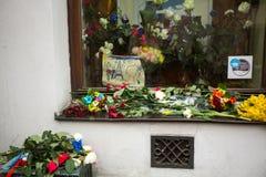 Folk satta stearinljus och blommor nära den allmänna konsulatet av Republiken Frankrike till Krakow Royaltyfri Fotografi