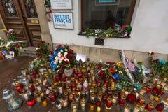 Folk satta stearinljus och blommor nära den allmänna konsulatet av Republiken Frankrike till Krakow Royaltyfria Bilder