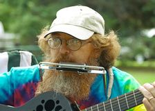 Folk singer. Plays a guitar and harmonica at an outdoor gathering Stock Photo