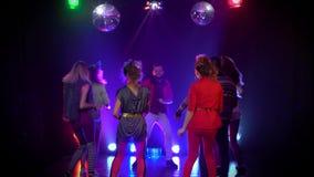 Folk som är glat och dansar på ljus för en strobe för nattklubb glödande stora objekt för bakgrundskontroll mer mycket min annan  stock video