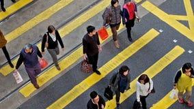 Folk som är rörande på övergångsställe i den fullsatta stadsgatan Hong Kong lager videofilmer