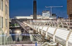 Folk som är rörande på milleniumbron på natten - London Arkivbild