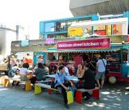 Folk som äter gatamat från en skåpbil i London UK Arkivbild
