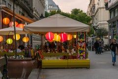 Folk som äter matställen på en utomhus- restaurang med färgrika lampor i den Budapest Ungern Fotografering för Bildbyråer