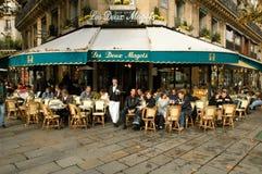 Folk som äter och dricker i en gatarestaurang av Paris royaltyfri foto