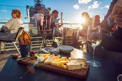 Folk som äter ost och dricker vin på takrestaurangen på solnedgångtid Arkivfoto