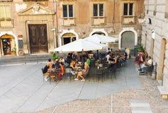 Folk som äter på det utomhus- kafét i Italien royaltyfria foton