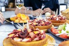 Folk som äter Pulpo en la Gallega med potatisar Galicianbläckfisk royaltyfria foton