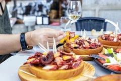Folk som äter Pulpo en la Gallega med potatisar Galicianbläckfiskdisk arkivfoto