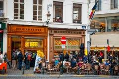 Folk som äter traditionella belgiska frites i Bryssel Royaltyfri Foto