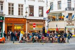 Folk som äter traditionella belgiska frites i Bryssel Royaltyfria Bilder
