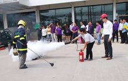 Folk som öva en branddrillborr som ut sätter en brand med en pulvertypeldsläckare Royaltyfri Foto