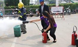 Folk som öva en branddrillborr som ut sätter en brand med en pulvertypeldsläckare Arkivfoton