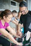Folk som övar på stationära cyklar i konditiongrupp Royaltyfria Foton