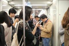 Folk som använder telefoner i tunnelbanan Arkivbild