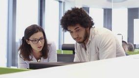Folk som arbetar det upptagna designkontoret med arbetare på skrivbord arkivfilmer