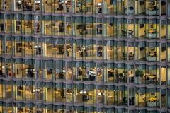 Folk som arbetar i en upptagen kontorsbyggnad Arkivbild