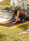 Folk som arbetar i mattan av blommor Royaltyfria Bilder