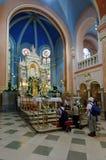 Folk som ber på relikskrin i en härlig kyrka på ambiental ljus Royaltyfria Bilder