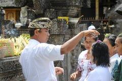 Folk som ber på Tirta Empul den hinduiska templet av Bali på Indonesien Royaltyfri Fotografi