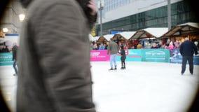 Folk som besöker Xmas-mässan på Alexanderplatz i Berlin Germany Främst barn och äldre folk som åker skridskor på is lager videofilmer
