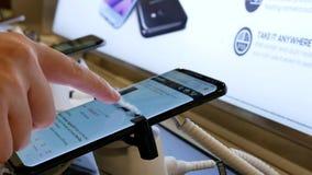 Folk som bläddrar amazon på mobiltelefonen för Samsung galax S8 arkivfilmer