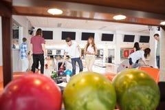 Folk som bowlar med bollar i förgrund Royaltyfri Fotografi