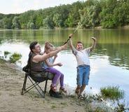 Folk som campar och fiskar, familjaktiv i natur, fisk som fångas på bete, flod och skog, sommarsäsong Royaltyfria Foton
