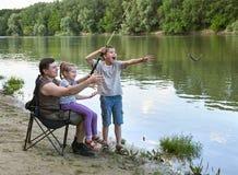 Folk som campar och fiskar, familjaktiv i natur, fisk som fångas på bete, flod och skog, sommarsäsong Royaltyfria Bilder