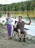 Folk som campar och fiskar, familjfritid i natur, fisk som fångas på bete, flod och skog, sommarsäsong Royaltyfri Bild