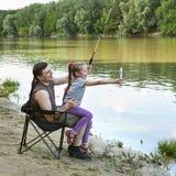 Folk som campar och fiskar, familjfritid i natur, fisk som fångas på bete, flod och skog, sommarsäsong Arkivfoton