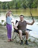 Folk som campar och fiskar, familjfritid i natur, fisk som fångas på bete, flod och skog, sommarsäsong Arkivfoto