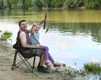 Folk som campar och fiskar, familjfritid i natur, fisk som fångas på bete, flod och skog, sommarsäsong Royaltyfria Bilder
